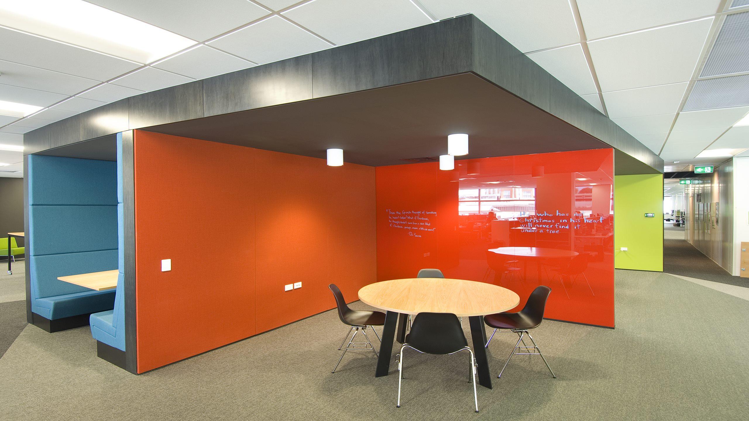 Premier Pinboard in orange fabric installed in an open plan meeting area.