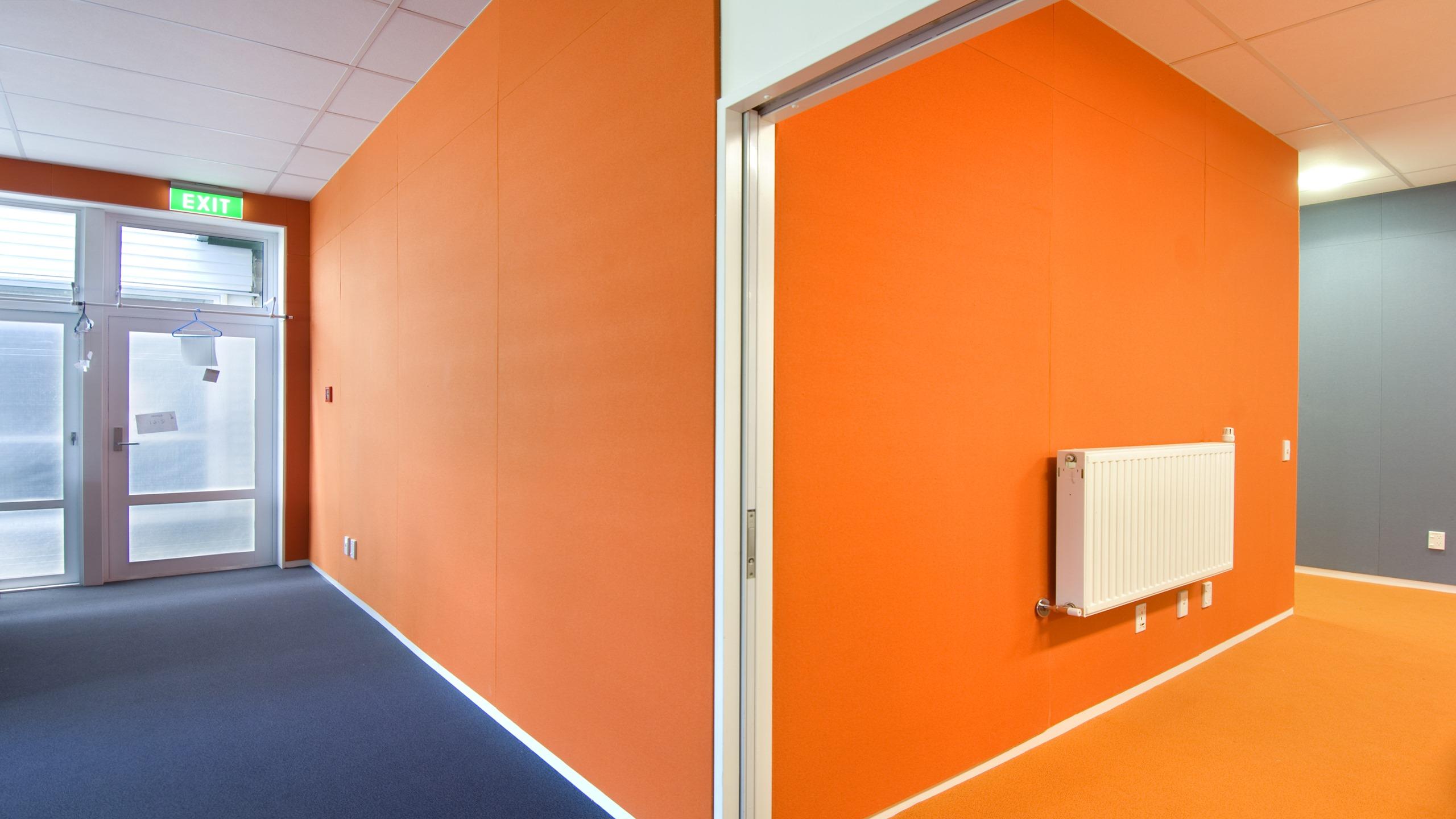 Premier Pinboard in orange fabric installed on to walls in a school hallway.