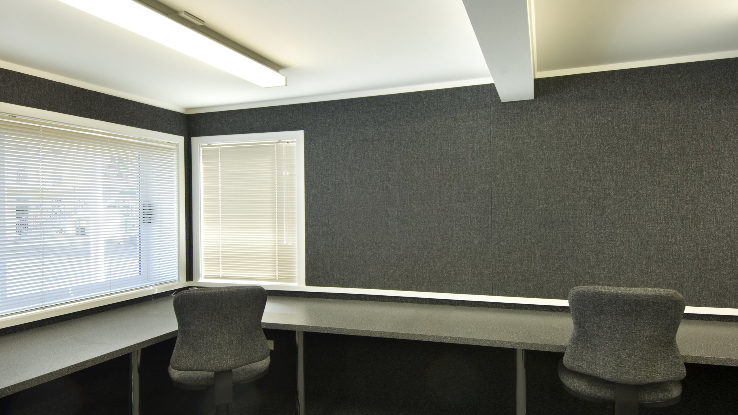 Premier pinboard installed in an office going around the windows and walls in charcoal grey fabric.