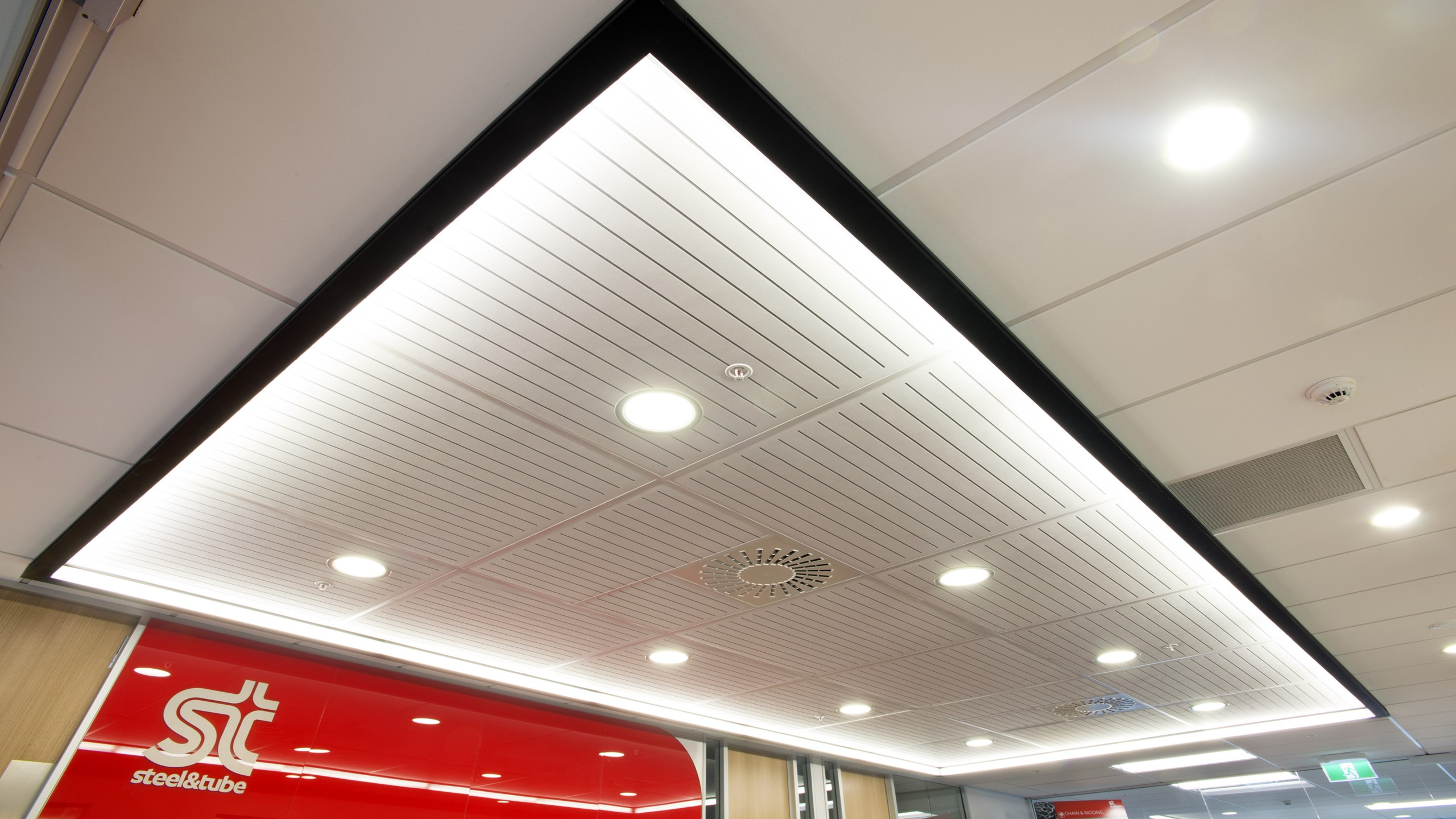 Steel & Tube HQ showing white Sonaris with S4 slot perforation pattern ceiling tiles installed into a suspended light raft above the reception area